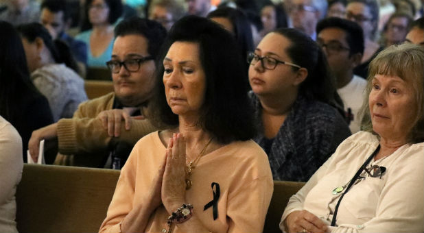People pray during an interfaith memorial service in Las Vegas.