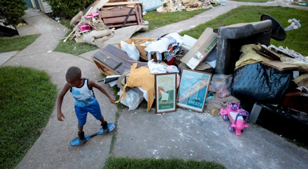 A little boy plays besides water-damaged items from his home.