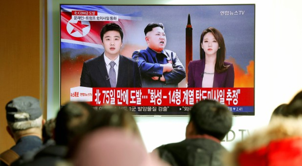 People watch a TV broadcasting a news report on North Korea firing what appeared to be an intercontinental ballistic missile (ICBM) that landed close to Japan.