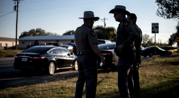 Members of the Wilson County Sheriff's office stand just inside taped off area near the First Baptist Church where a shooting left many dead and injured in Sutherland Springs, Texas.
