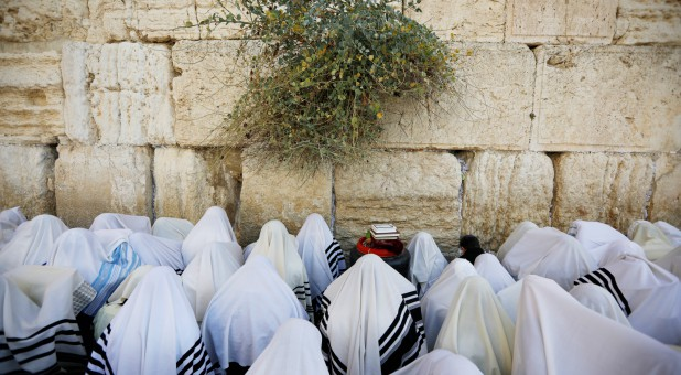 Jewish worshippers, covered in prayer shawls, take part in the priestly blessing during the Jewish holiday of Sukkot, at the Western Wall.