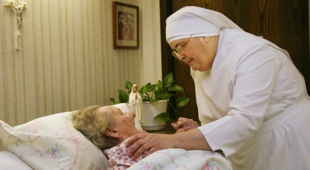 One of the Little Sisters of the Poor caring for an elderly woman.