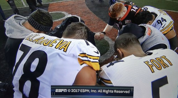Andy Dalton (14) prays with his opponents for one of their teammates.