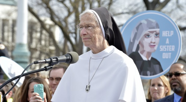 A nun speaks at a rally.