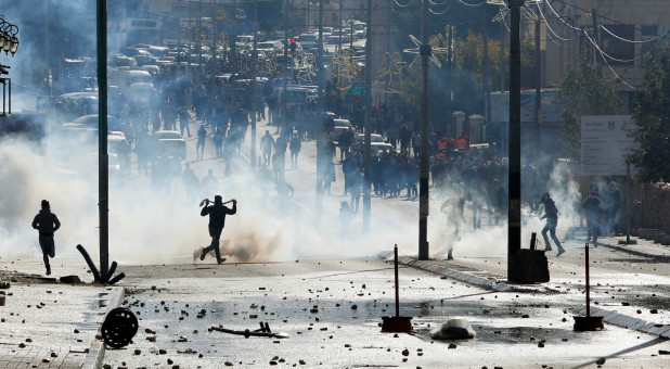 Palestinian protesters run for cover from tear gas fired by Israeli troops during clashes at a protest against U.S. President Donald Trump's decision to recognize Jerusalem as the capital of Israel.