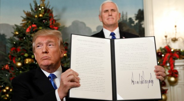 U.S. Vice President Mike Pence stands behind as U.S. President Donald Trump holds up the proclamation he signed that the United States recognizes Jerusalem as the capital of Israel and will move its embassy there.