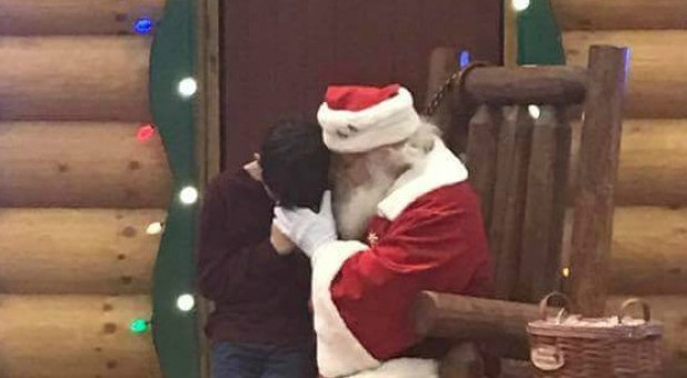 A little boy prays with Santa.