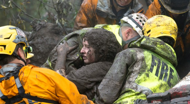 Emergency personnel carry a woman rescued from a collapsed house after a mudslide in Montecito, California.