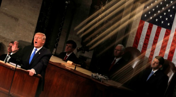 U.S. President Donald Trump and Vice President Mike Pence (C) are seen behind the reflection of a House chamber railing as Trump delivers his State of the Union address.