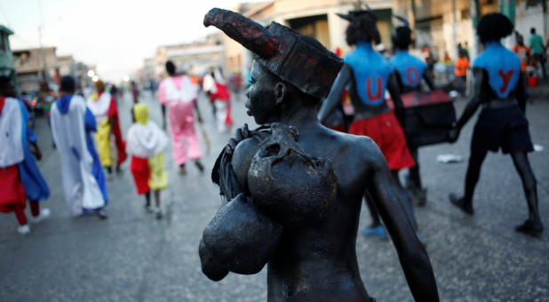 A reveller carrying two skulls parades along a street at the Carnival of Port-au-Prince, Haiti.