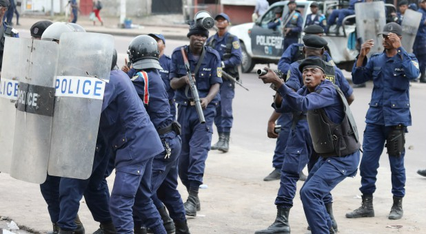 Policemen react after a protester threw a stone from Notre Dame Cathedral compound in Kinshasa, Democratic Republic of Congo.