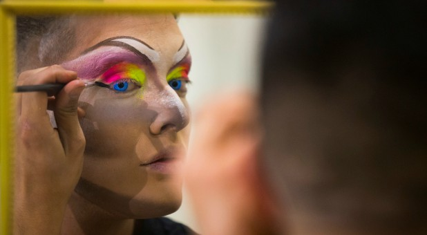 A participant prepares to perform in a drag queen competition during carnival festivities.