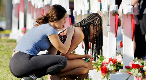 A senior at Marjory Stoneman Douglas High School weeps in front of a cross and Star of David for shooting victim Meadow Pollack while a fellow classmate consoles her at a memorial by the school in Parkland, Florida.