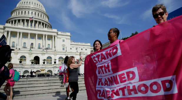 Health care activists with Planned Parenthood and the Center for American Progress protest.