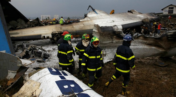 Rescue workers work at the wreckage of a US-Bangla airplane after it crashed at the Tribhuvan International Airport in Kathmandu, Nepal.