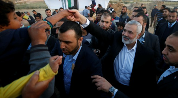 Palestinian Hamas Chief Ismail Haniyeh shakes hands with a boy during a protest demanding the right to return to their homeland, at the Israel-Gaza border, east of Gaza City.