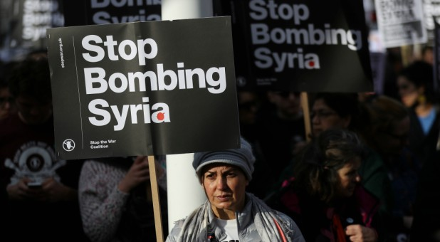 Protesters hold placards during a demonstration against bombing Syria outside the Houses of Parliament in London, Britain.