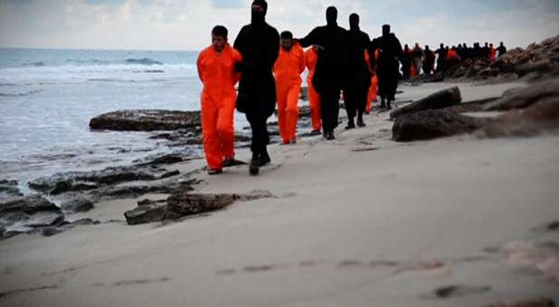 Men in orange jumpsuits purported to be Egyptian Christians held captive by the Islamic State (IS) are marched by armed men along a beach.