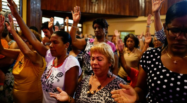 People react during a religious ceremony where victims of the Boeing 737 plane crash were remembered at a church in Havana, Cuba.