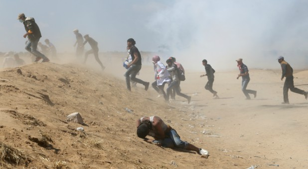 A Palestinian demonstrator reacts as others run from tear gas fired by Israeli forces during a protest.