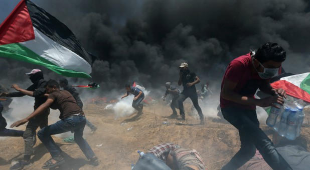Palestinian demonstrators run for cover from Israeli fire and tear gas during a protest against U.S. Embassy move to Jerusalem.