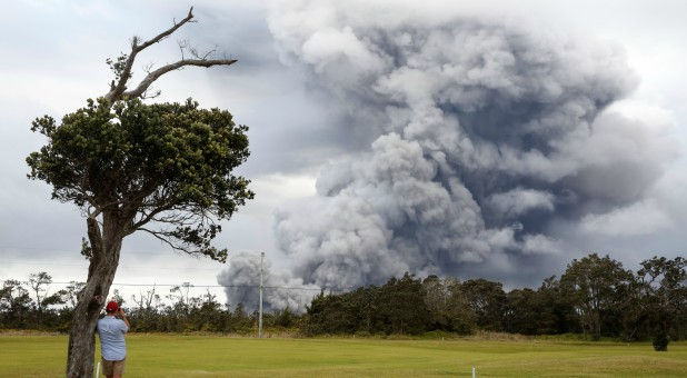 A man watches as ash erupts from the Halemaumau crater near the community of Volcano during ongoing eruptions of the Kilauea Volcano in Hawaii.