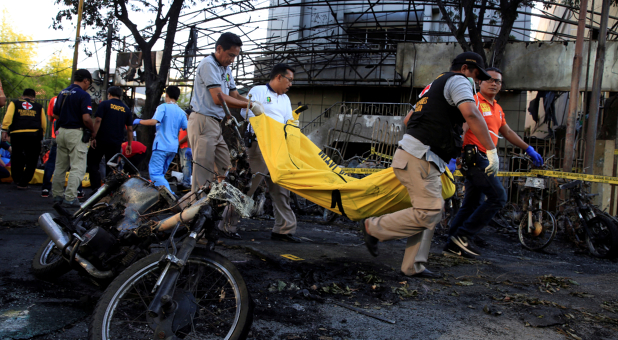 Paramedics remove a body near burned motorcycles following a blast at the Pentecost Church Central Surabaya (GPPS), in Surabaya, Indonesia.