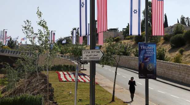 A woman walks next to a road sign directing to the U.S. Embassy, in the area of the U.S. consulate in Jerusalem.