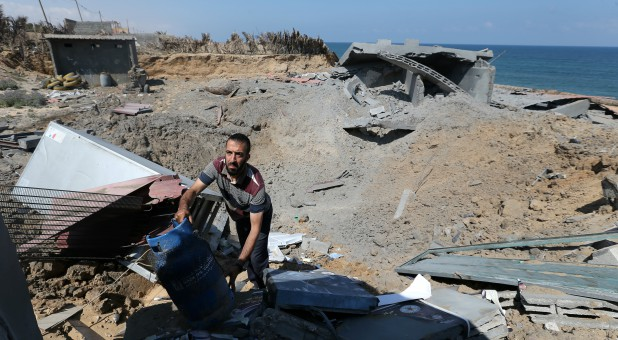 A Palestinian man inspects a destroyed Islamic Jihad military base after it was targeted by an Israeli warplane.