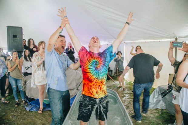 A man praises the Lord after his baptism at Bonnaroo.