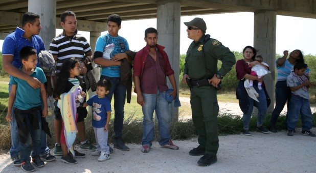 Border patrol agent Sergio Ramirez talks with immigrants who illegally crossed the border from Mexico into the U.S.
