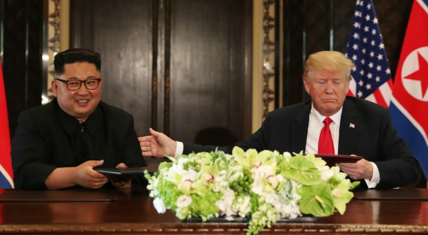 U.S. President Donald Trump and North Korea's leader Kim Jong Un attend a signing ceremony during a summit.