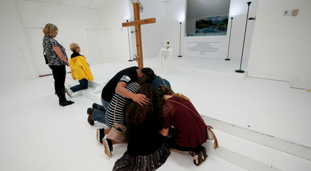 People pray in the First Baptist Church of Sutherland Springs, where 26 people were killed in a shooting attack in November.