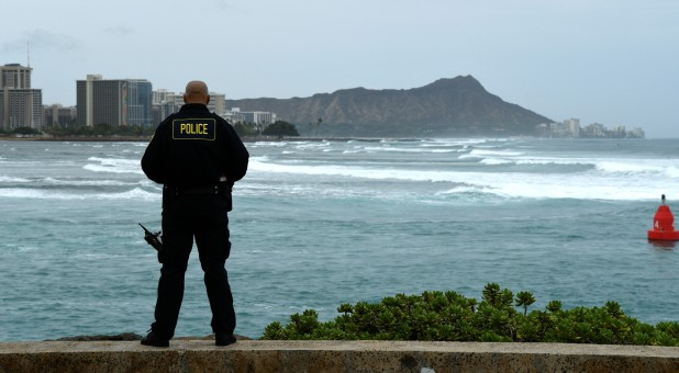 Honolulu police officer Chad Asuncion monitors the water conditions and warns surfers about the conditions as Hurricane Lane approaches Honolulu, Hawaii.