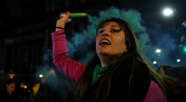 An abortion rights activist holds a flare outside the Congress after senators rejected a bill to legalize abortion, in Buenos Aires, Argentina.