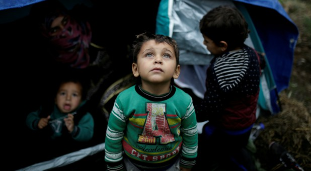A Syrian refugee boy stands in front of his family tent at a makeshift camp for refugees and migrants next to the Moria camp on the island of Lesbos, Greece.