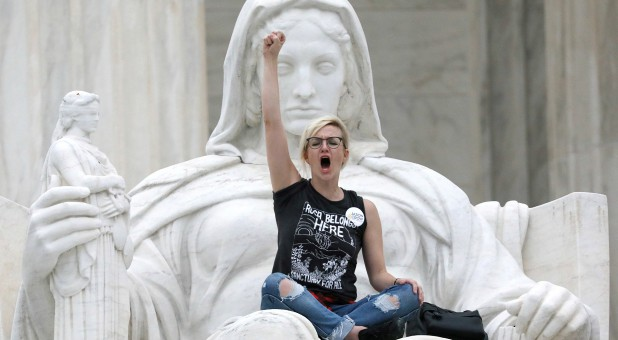"A protester sits on the lap of ""Lady Justice"" on the steps of the U.S. Supreme Court building."