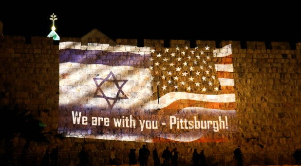 """An image of Israeli and American flags with the wording, """"We are with you - Pittsburgh"""" is projected on the walls of Jerusalem's Old City."""