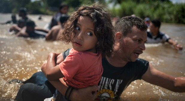 A father carries his daughter across a river as part of the caravan of migrants en route to the U.S.