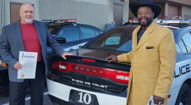 Pastors pose with police car with national motto for Clergy Appreciation Month in 2017.