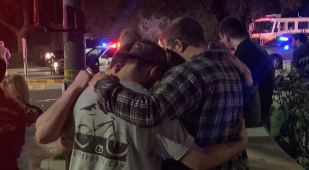 People stand behind cordon tape and hold each other after the shooting in Thousand Oaks, California, U.S., Nov. 8, 2018 in this image obtained from social media.
