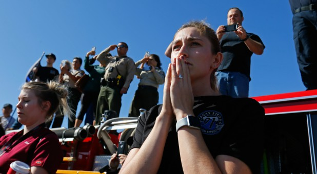 Madison Fuller of Thousand Oaks reacts as she watches from an overpass as a procession for the body of Sergeant Ron Helus, who died in a shooting incident at a Thousand Oaks bar, drives down Ventura HIghway 101 in Thousand Oaks, California.