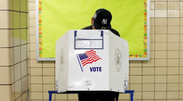A man wearing a New York Yankees hat votes during the midterm election at P.S. 140 in Manhattan.