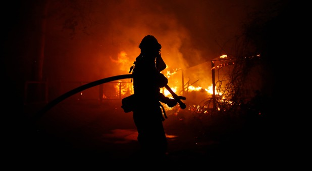 A firefighter battles the Woolsey Fire in Malibu, California.
