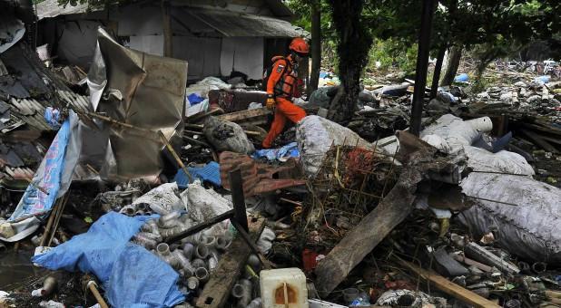 Rescue worker walks as he searches for victims among debris after a tsunami hit Sunda Strait at Carita district in Pandeglang, Indonesia, Dec. 25, 2018.