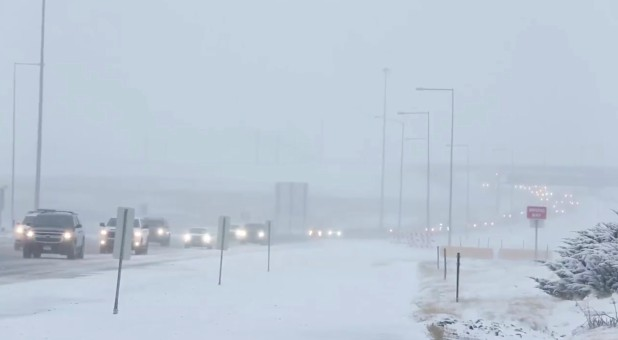 Cars move along a snow-covered road in Denver.