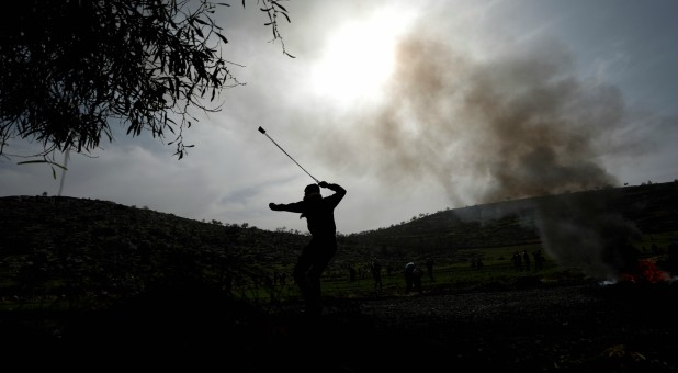 A Palestinian uses a sling to hurl stones at Israeli forces during clashes in al-Mughayer village near Ramallah, in the Israeli-occupied West Bank.