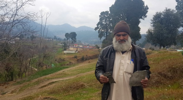 Fida Hussain, 46, holds what he believes to be fragments of payload released by the Indian military aircrafts, in Jaba village, Pakistan.
