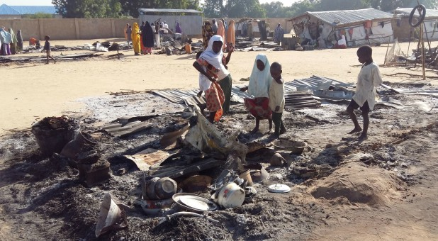 People stand amid the damage at a camp for displaced people after an attack by suspected members of the Islamist Boko Haram insurgency.