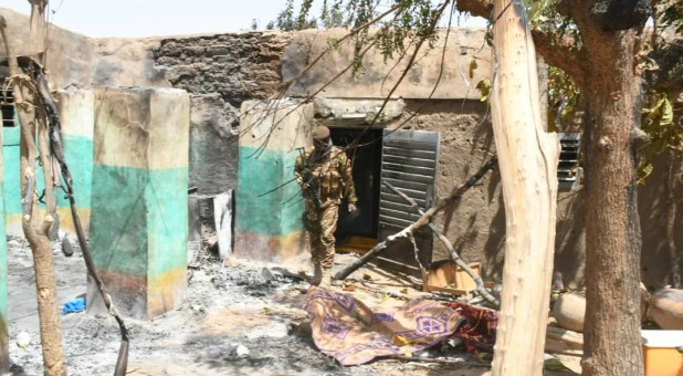 A soldier walks amid the damage after an attack by gunmen on Fulani herders.